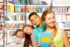Quattro bambini che stanno in una fila dentro la biblioteca Immagini Stock
