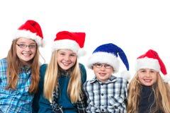 Quattro bambini con sorridere dei cappelli di natale Fotografia Stock