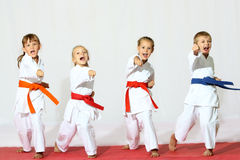 Quattro bambini in kimono hanno colpito una perforazione su un fondo bianco fotografia stock libera da diritti