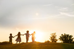Quattro bambini stanno giocando sul tramonto Fotografia Stock Libera da Diritti