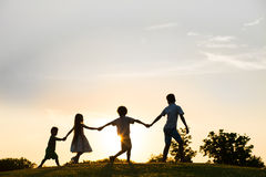 Quattro bambini stanno giocando sul tramonto Fotografie Stock
