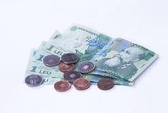 Quattro banconote degno 1 leu rumeno con parecchie monete degno 10 e 5 rumeno Bani su un fondo bianco Immagini Stock