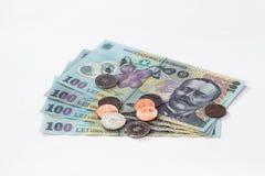 Quattro banconote degno 100 rumeno Lei con parecchie monete degno 10 e 5 rumeno Bani isolate su un fondo bianco Fotografia Stock Libera da Diritti
