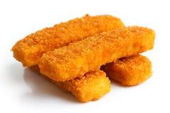Quattro bastoncini di pesce fritti dorati impilati su bianco fotografia stock libera da diritti