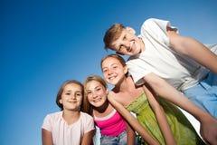 Quattro bei bambini felici che esaminano macchina fotografica dalla cima nel giorno e nel cielo blu di estate soleggiati esaminan Fotografia Stock Libera da Diritti
