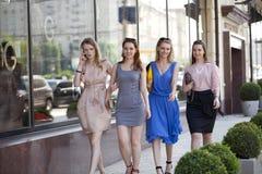 Quattro belle ragazze di modo che camminano sulla via Immagine Stock