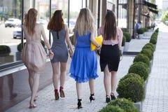 Quattro belle ragazze di modo che camminano sulla via Immagini Stock