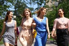 Quattro belle ragazze di modo che camminano sulla via Fotografie Stock Libere da Diritti