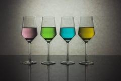 Quattro bicchieri d'acqua colorati Immagini Stock