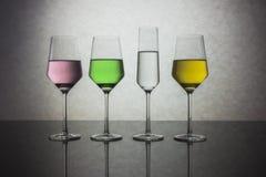 Quattro bicchieri d'acqua colorati Fotografia Stock