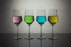Quattro bicchieri d'acqua colorati Fotografie Stock Libere da Diritti