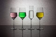 Quattro bicchieri d'acqua colorati Fotografia Stock Libera da Diritti