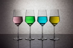 Quattro bicchieri d'acqua colorati Immagine Stock