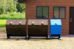 Quattro bidoni della spazzatura della prova dell'orso con un recipiente di riciclaggio fotografia stock libera da diritti