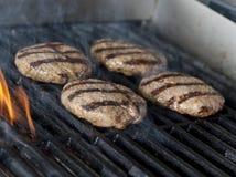 Quattro bistecche dell'hamburger della carne di pollo sulla griglia con le fiamme Cookin Immagini Stock Libere da Diritti