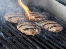 Quattro bistecche dell'hamburger della carne di pollo sulla griglia con le fiamme Cookin Immagini Stock