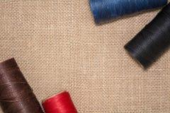 Quattro bobine dei fili su un fondo di tela Fili rossi, blu, marroni e neri Immagini Stock Libere da Diritti