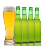 Quattro bottiglie da birra e vetro pieno Fotografie Stock