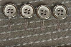 Quattro bottoni sul tessuto Immagini Stock