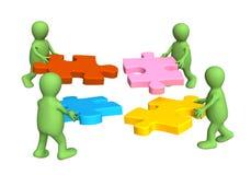 Quattro burattini, tenenti in mani un puzzle Fotografia Stock