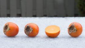 Quattro cachi su ghiaccio Metà di frutta e di tre interi cachi Immagine Stock Libera da Diritti
