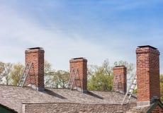 Quattro camini con le diverse scale sul tetto immagine stock