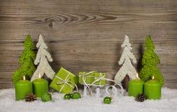 Quattro candele brucianti verdi di natale con i presente e gli alberi sopra Immagini Stock