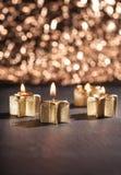 Quattro candele dorate di arrivo accese con il fondo del bokeh Fotografie Stock