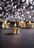Quattro candele dorate di arrivo accese con il fondo del bokeh Immagine Stock