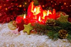 Quattro candele rosse di arrivo con la decorazione e la neve di natale Fotografia Stock Libera da Diritti
