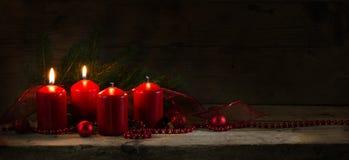 Quattro candele rosse, due di loro combustione sul secondo arrivo, chri Fotografie Stock