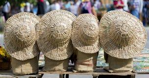 Quattro cappelli di paglia delle dimensioni differenti sulle borse di tela fotografie stock