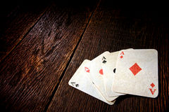 Quattro carte d'annata della mazza degli assi sulla vecchia Tabella del salone Immagini Stock