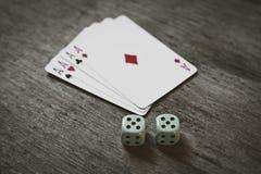 Quattro carte da gioco degli assi e due dadi numerano il doppio cinque su un fondo di legno rischio, fortuna, astrazione Immagine Stock