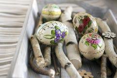 Quattro casalinghi e le uova di Pasqua fatte a mano con le immagini del fiore sulla betulla si ramificano, ornamenti cechi, picco immagini stock libere da diritti