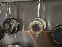 Quattro casseruole d'acciaio con i fondi bruciati che appendono in cucina industriale fotografia stock