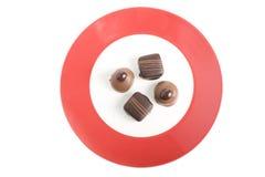 Quattro cioccolato gastronomici sulla zolla rossa Immagini Stock Libere da Diritti