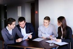 Quattro colleghi dell'uomo e della donna si riuniscono per la riunione all'ufficio di Immagine Stock Libera da Diritti