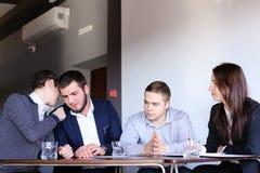 Quattro colleghi dell'uomo e della donna si riuniscono per la riunione all'ufficio di Fotografie Stock Libere da Diritti