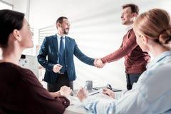 Quattro colleghi energetici che finiscono riunione fotografia stock