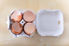 Quattro coperture rotte dell'uovo in contenitore dell'uovo Fotografia Stock Libera da Diritti