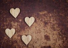 Quattro cuori di legno su un faux grungy rivestono di pelle il materiale Immagini Stock