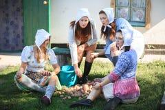 Quattro donne quattro donne che vagliano le patate nell'iarda vicino alla casa Vita rurale, retro stile immagine stock libera da diritti