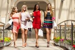 Quattro donne di compera che camminano nel negozio Immagine Stock