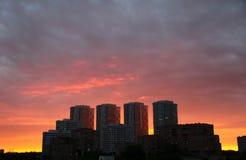 Quattro edifici residenziali sui precedenti del tramonto Immagine Stock