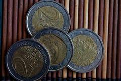 Quattro euro monete si trovano sulla denominazione di bambù di legno della tavola è euro due immagine stock libera da diritti