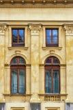 Quattro finestre su una parete gialla Fotografie Stock