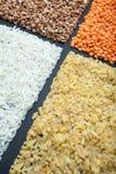 Quattro generi di cereali organici: riso, bulgur, grano saraceno e lenticchie su un fondo nero fotografie stock