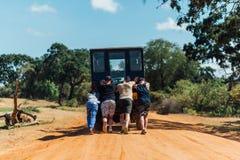 Quattro genti che spingono un'automobile che ha attaccato nella sabbia in savana Immagini Stock