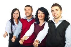 Quattro genti di affari che danno i pollici Immagini Stock